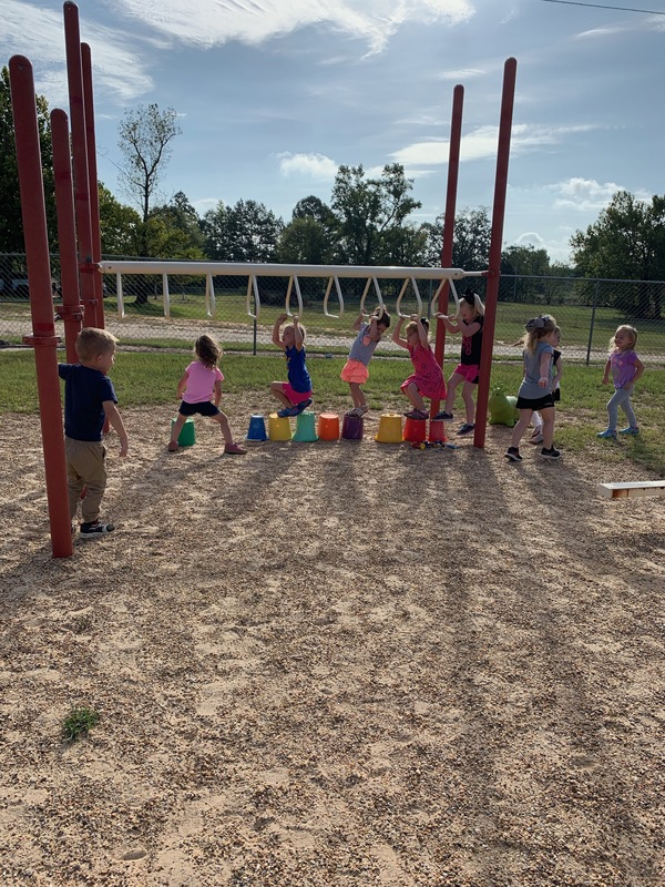 Preschool Students Playing on the Monkey Bars