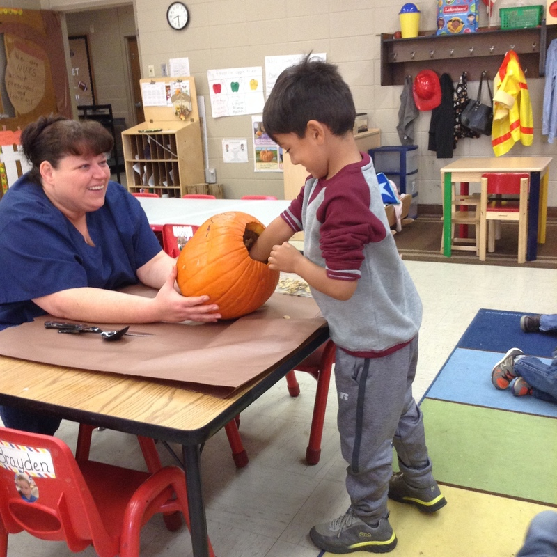 Mrs. Toyna Holding the Pumpkin to Help students Remove the Seeds Inside
