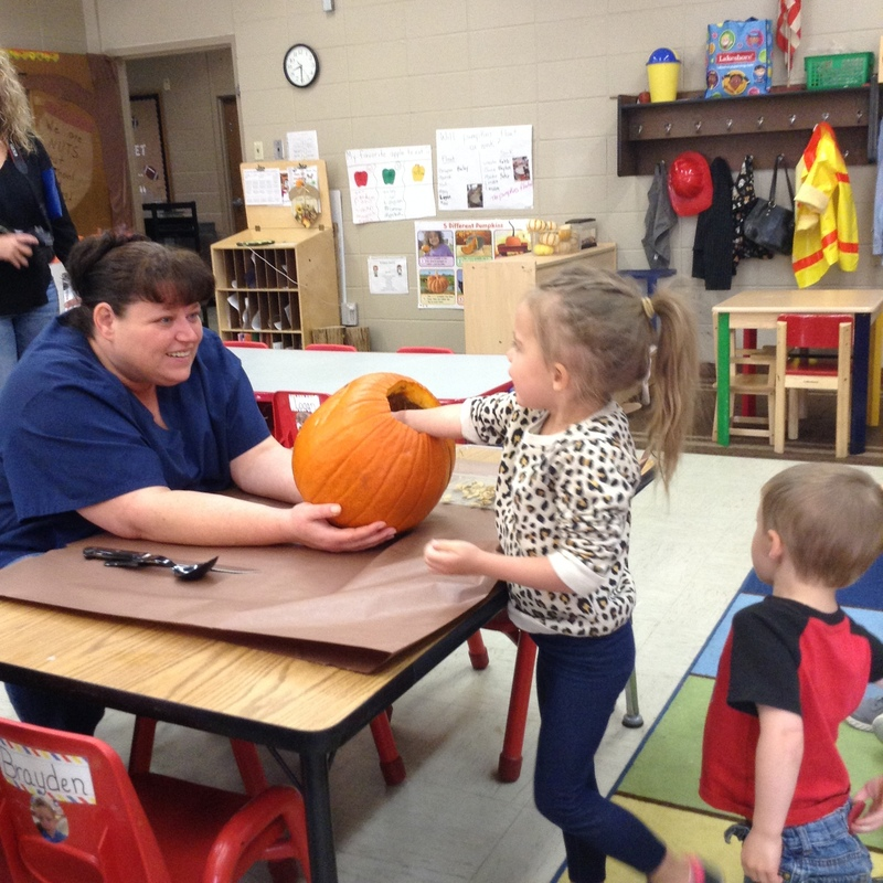 Mrs. Toyna Holding the Pumpkin to Help students Remove the Seeds Inside Pic 2