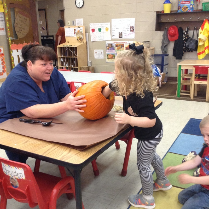 Mrs. Toyna Holding the Pumpkin to Help students Remove the Seeds Inside Pic 3
