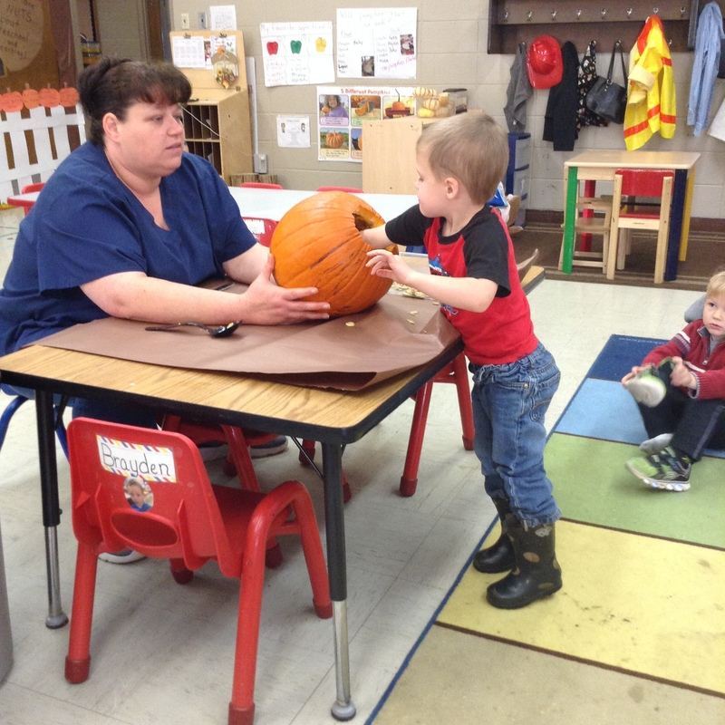 Mrs. Toyna Holding the Pumpkin to Help students Remove the Seeds Inside Pic 4