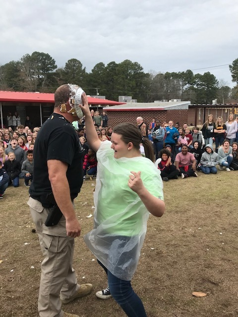 Student Emilee Hodges Throwing a Pie at Officer Hodges